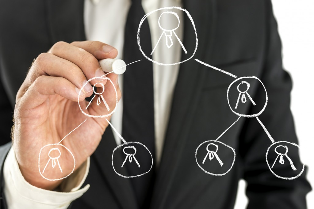 Business manager drawing business hierarchy on virtual screen.